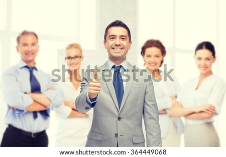 happy businessman in suit showing thumbs up - stock photo