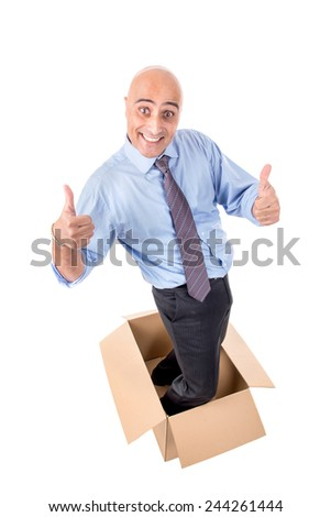 Happy businessman inside a cardboard box - stock photo