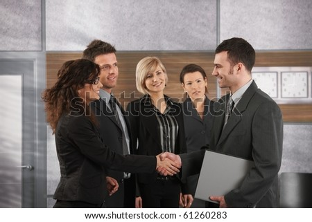 Happy businessman introducing himself to business team in office.? - stock photo