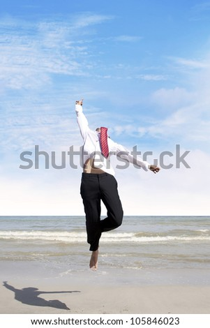 Happy businessman jumping at the beach to celebrate his success