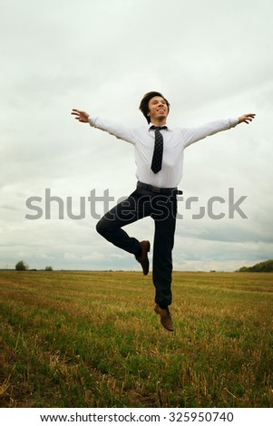 Happy businessman jumping in a field  - stock photo