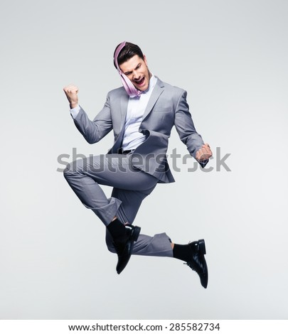 Happy businessman jumping in air over gray background - stock photo