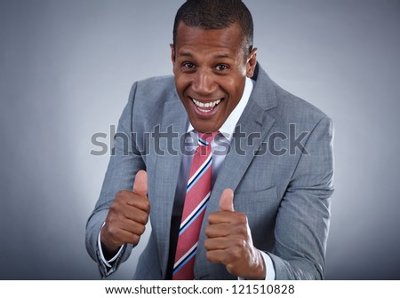 Happy businessman keeping his thumbs up with smile over grey background - stock photo