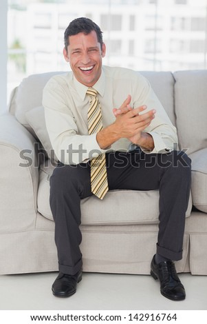 Happy businessman laughing on the couch