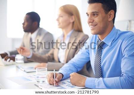 Happy businessman listening to explanations at seminar on background of colleagues - stock photo