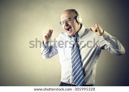 Happy businessman listening to music - stock photo