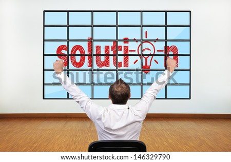 happy businessman looking at solution on plasma in office - stock photo