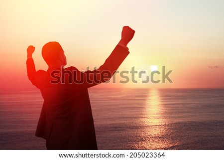 happy businessman looking at sunrise - stock photo