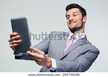 Happy businessman looking at tablet computer over gary background