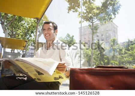 Happy businessman looking away while reading newspaper at bus stop - stock photo