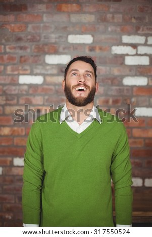 Happy businessman looking up while standing against brick wall