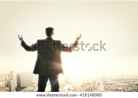 Happy businessman looks sunrise in city, concept for business - stock photo