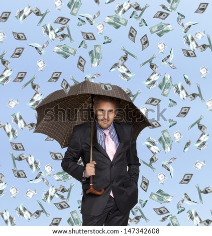 Happy businessman man with umbrella and flying dollar banknotes against blue sky  - stock photo