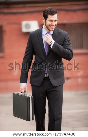 happy businessman on the street smiling and fixing his tie - stock photo