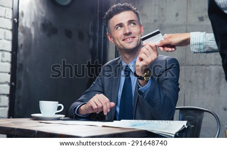 Happy businessman passing his credit card to waiter in cafe - stock photo