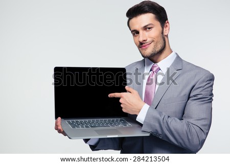 Happy businessman pointing finger on the laptop screen over gray background. Looking at camera - stock photo