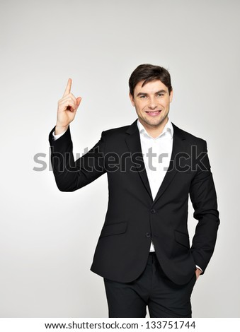Happy businessman points his finger up  in black suit at studio - stock photo