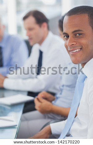 Happy businessman posing in the meeting room while colleagues are working behind