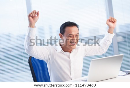 Happy businessman raised his hands with excitement and looking at laptop - stock photo