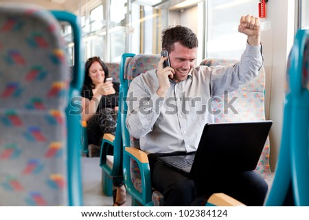 Happy businessman receiving good news on a train. selective focus. - stock photo
