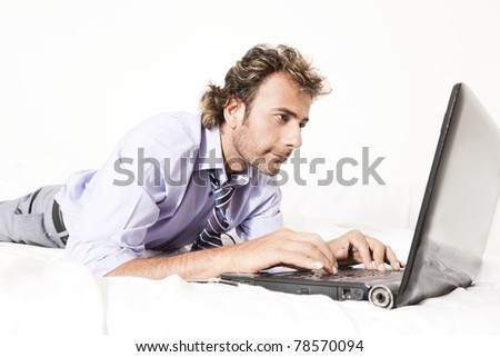 happy businessman relaxing in the bed and working on the laptop