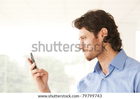 happy businessman sending or reading an message on a mobile phone - stock photo
