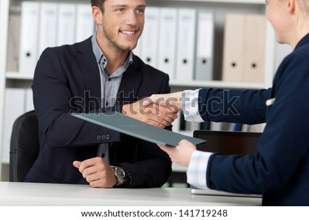 Happy businessman shaking hands with a female interviewer in office - stock photo