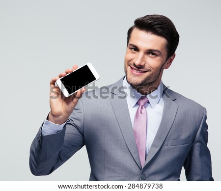 Happy businessman showing blank screen smartphone over gray background and looking at camera - stock photo