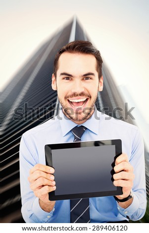 Happy businessman showing his tablet pc against skyscraper - stock photo