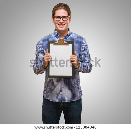Happy Businessman Showing Paper On Clipboard against a grey background