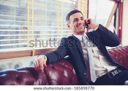 Happy businessman sitting and talking on the phone at office - stock photo