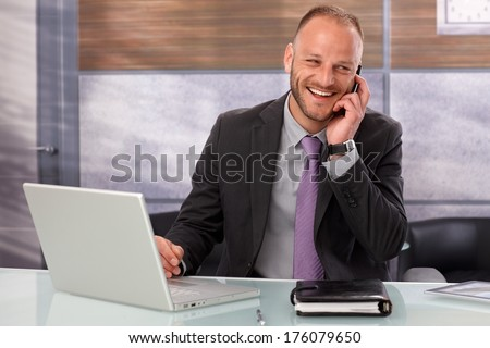 Happy businessman sitting at desk in office, talking on mobilephone, smiling happy. - stock photo