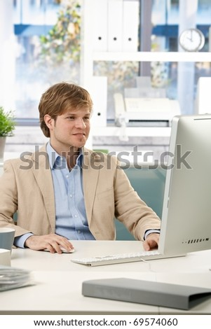Happy businessman sitting at desk in office working with computer, looking at screen.? - stock photo
