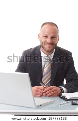 Happy businessman sitting at desk, working with laptop computer, smiling, looking at camera. White background.