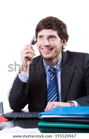 Happy businessman sitting at the desk and calling