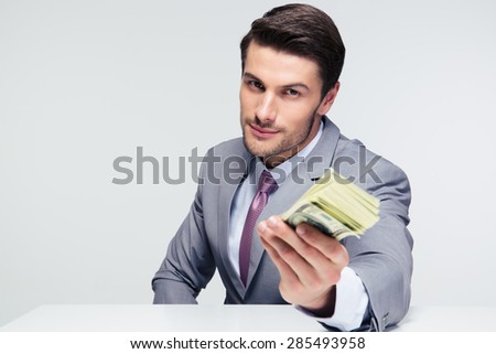 Happy businessman sitting at the table and giving money on camera over gray background - stock photo