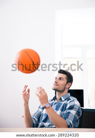 Happy businessman sitting at the table and throwing ball in office - stock photo