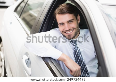 Happy businessman sitting in drivers seat in his car - stock photo
