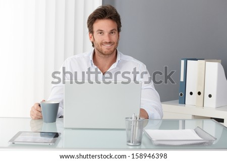 Happy businessman sitting in office, working with laptop computer, having tea, smiling at camera.