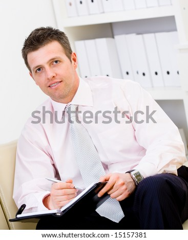 Happy businessman sitting on sofa at office and writing to notebook, smiling.