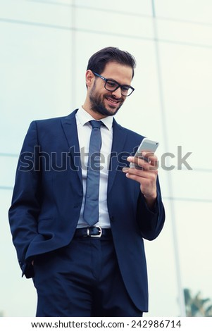 Happy businessman smiling as he reads a text message standing outside the office - stock photo