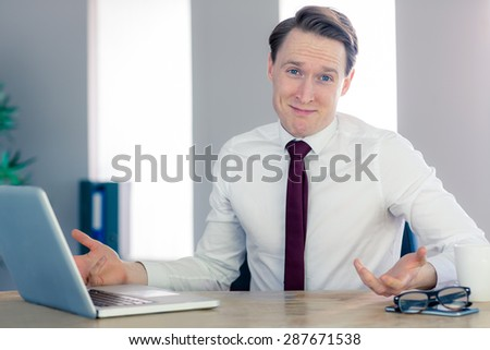 Happy businessman smiling at camera in his office