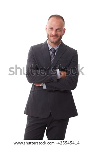 Happy businessman standing arms crossed over white background, smiling, looking at camera.
