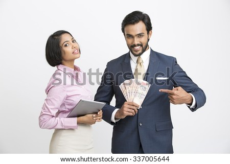 Happy businessman standing holding rupees with his businesswoman on white background. - stock photo