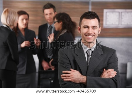Happy businessman standing in office in front of business team. - stock photo
