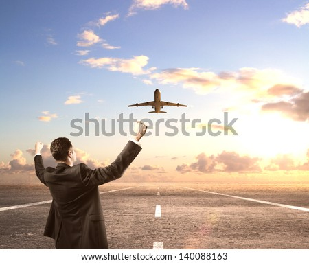 happy businessman standing on runway and looking on airplane