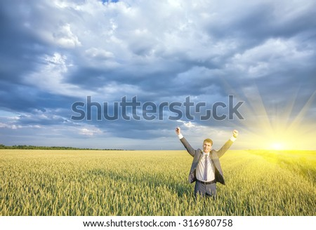 Happy businessman standing on the field to face the sky - stock photo