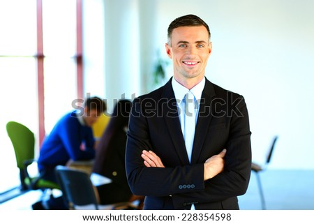 Happy businessman standing with arms folded in front of colleagues - stock photo