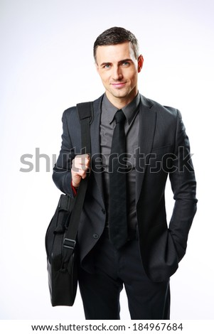 Happy businessman standing with bag over gray background - stock photo