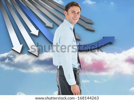 Happy businessman standing with hand in pocket against bright white hall with columns